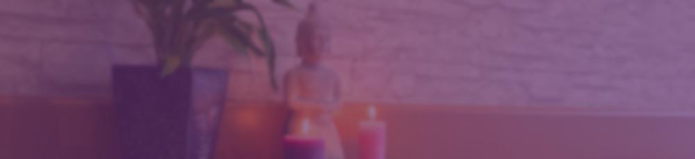 Buddha und Kerze vor Wand